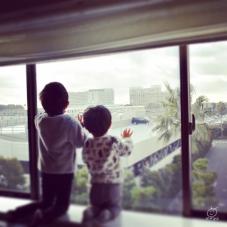 ホテルの窓から、モノレールを眺める兄弟。